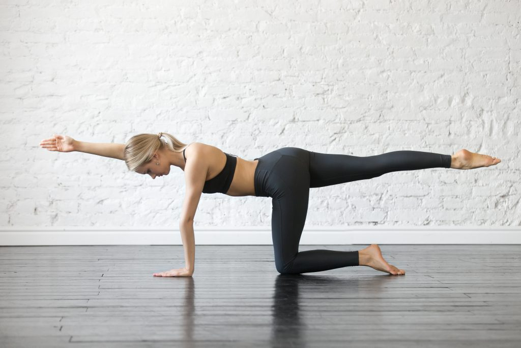 Young attractive woman practicing yoga, stretching in Bird dog exercise, Donkey kick pose, working out, wearing sportswear, black top and pants, indoor full length, studio background